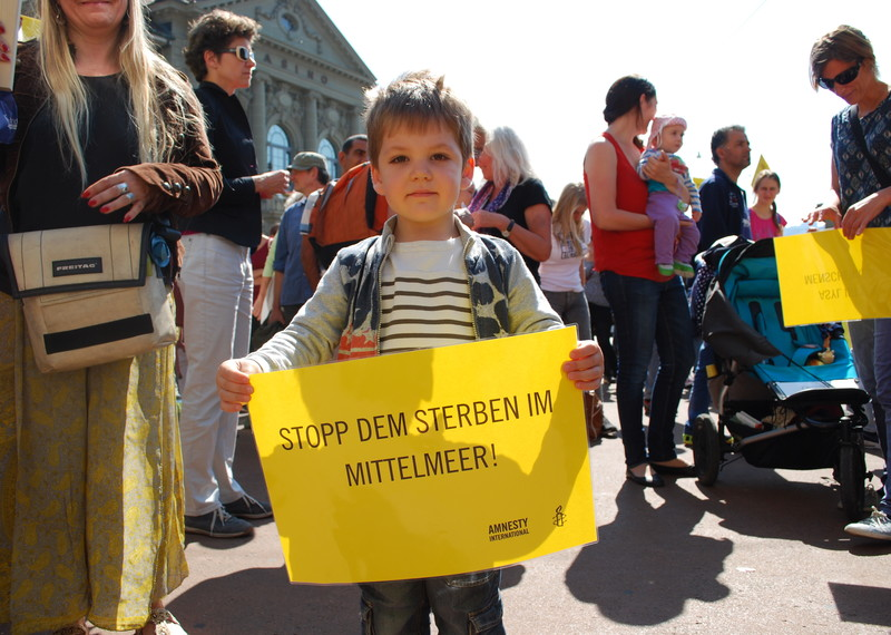A young boy shows solidarity with refugees at a demonstration in Berne, Switzerland, September 2015 © Amnesty International