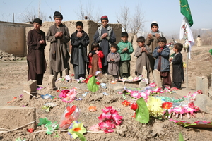 Orphaned children of Dawood and Zahir praying by the graveyard where their father, uncle, aunts and cousins are buried after being killed by US/NATO air strikes in Afghanistan. © Amnesty International