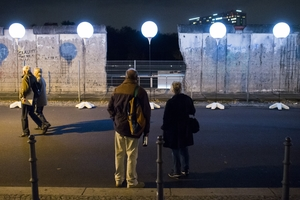 People walk past the light installation Lichtgrenze (Light border) on the course of the former Berlin wall in Berlin ©AFP/Getty Images.