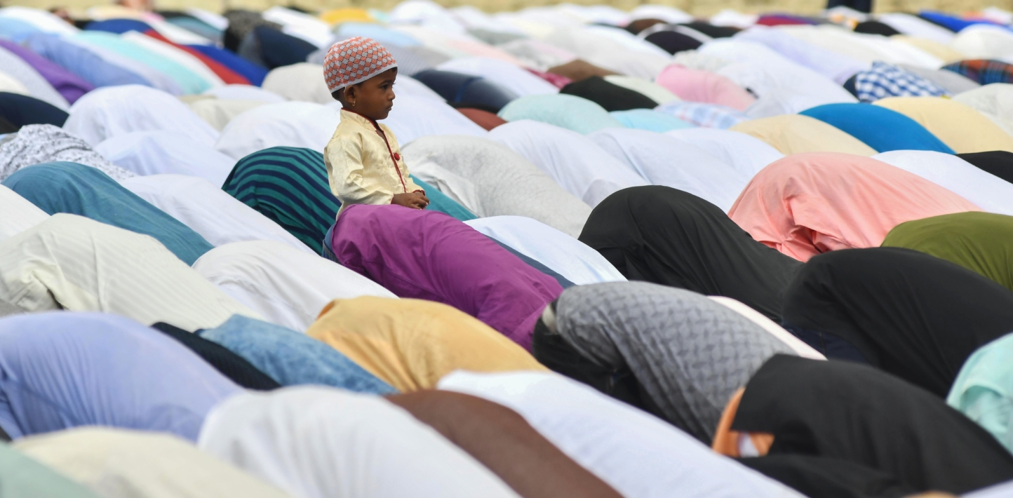 An Indian child looks on as Muslims offer prayers to mark the Eid al-Adha festival in Guwahati in northeast Assam state on August 22, 2018. - Muslims across the world are celebrating the annual festival of Eid al-Adha, or the Festival of Sacrifice, in commemoration of Prophet Abraham's readiness to sacrifice his son to show obedience to God.