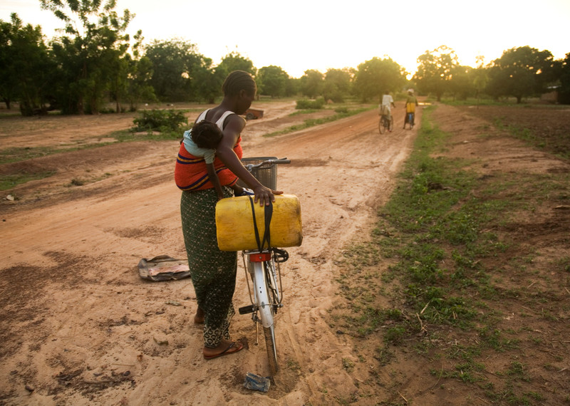 A woman carrying a baby on her back sets off on her bicycle to get water as the day closes.