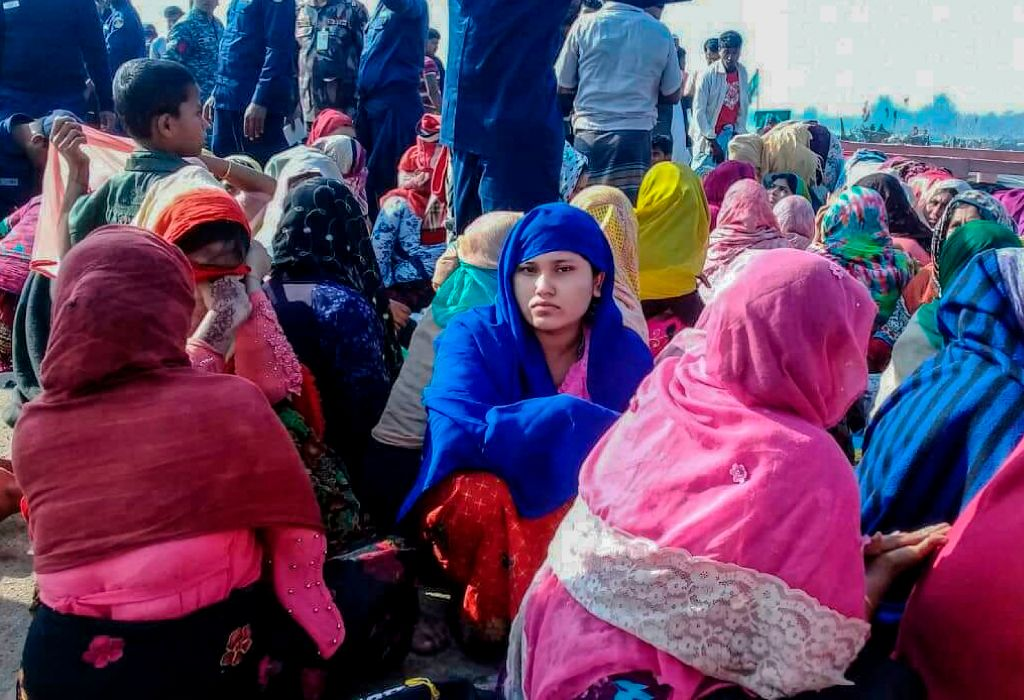 Rohingya refugees wait in an area following a boat capsizing accident, in Teknaf on February 11, 2020. - At least 14 people drowned and dozens more were unaccounted for after a boat carrying Rohingya refugees sank off southern Bangladesh early February 11, officials said.