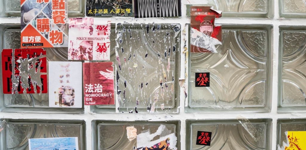 Stickers with messages in support of the pro-democracy movement are scraped from a wall outside a restaurant in Hong Kong.