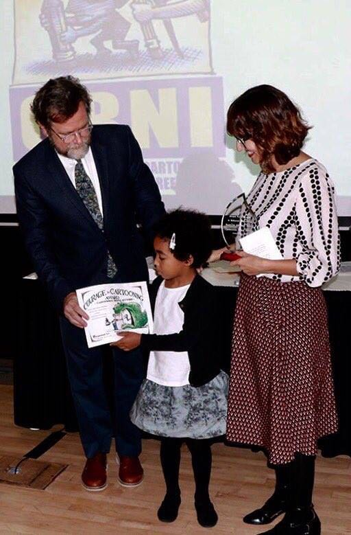 Ramon 's wife and daughter receiving on 2 November the 2017 Award for Courage in Editorial Cartooning from the Cartoonists Rights Network International