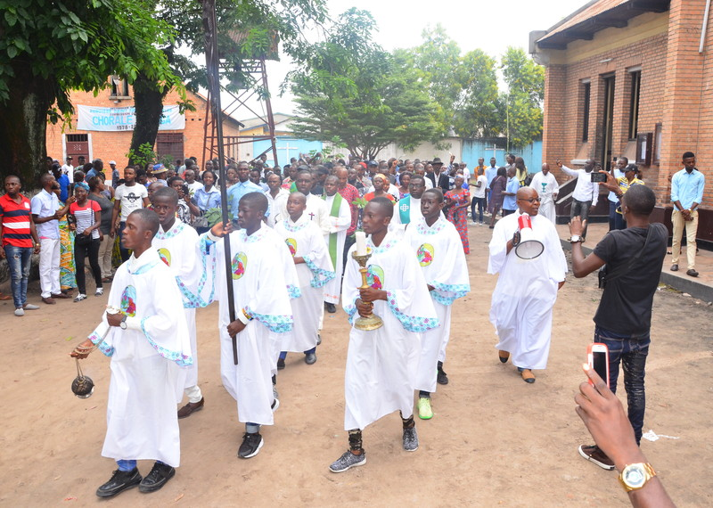 Congregants start a peaceful protests carrying palms and an altar boys carrying a cross, candle and a censer at St. Francois de Sales.