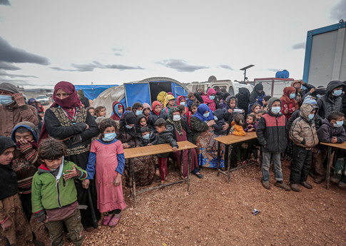 People, mostly children, wear masks as a preventive measure against COVID-19 as Idlib Health Directorate and Civil Defense Crews along with local charities carry out disinfection works at schools and tent cities in Idlib, Syria on 18 March, 2020. © Anadolu Agency/Getty Images