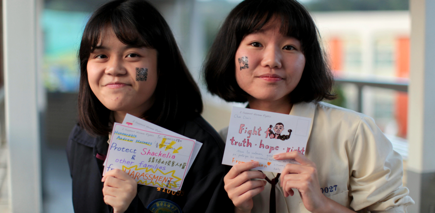 Students take hold up messages written on cards