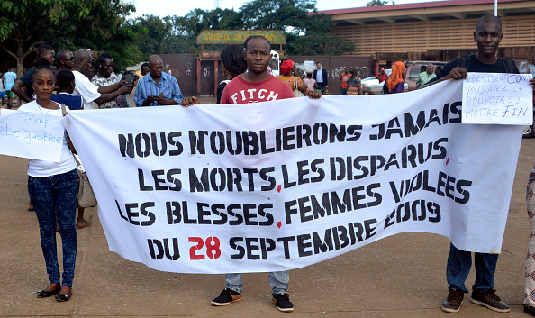 People hold a banner reading 'We will never forget the dead, the missing, the wounded and the raped women of September 28, 2009' in Conakry on September 28, 2016 as they mark the seventh anniversary of an opposition rally during which 157 demonstrators were killed when security forces opened fire on them