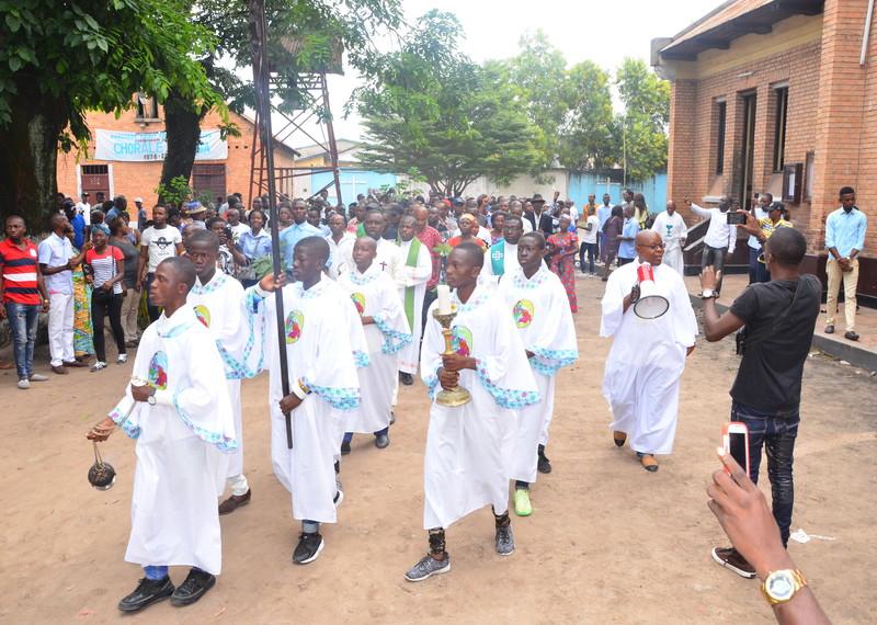 Manifestation pacifique de fidèles brandissant des rameaux avec des enfants de chœur portant une croix, une bougie et un encensoir à la paroisse Saint-François de Sales.
